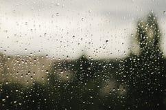 Дождевые капли на окне с расплывчатыми деревьями как предпосылка зонтик ненастного песочного сезона пляжа тропический Стоковое Изображение RF