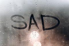 Дождливая погода, надпись грустная на потном стекле стоковые фотографии rf