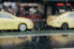 Дождливое окно с автомобилями такси запачканными в предпосылке стоковые фотографии rf
