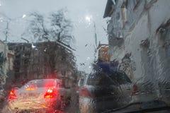 Дождливый день в городе, движении и падениях nad автомобилей дождя на лобовом стекле автомобиля Стоковое фото RF