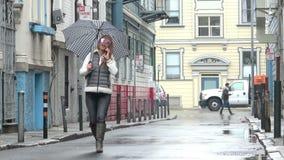 дождь Женщина идя вниз с улицы города говоря на ее сотовом телефоне сток-видео