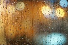 Дождь падает на стеклянное окно с предпосылкой bokeh Стоковое Изображение RF