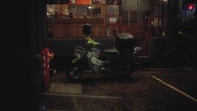 Дождь старого скутера сильный в городе ночи сток-видео