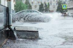 Дождевая вода пропуская от водосточной трубы металла во время потока брызгает предпосылки автомобилей предохранение от концепции  Стоковое Фото