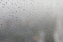Дождевая капля, вода падает на стеклянную поверхность окна Стоковая Фотография RF