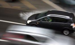 Дождливый день в городе: Управляющ автомобилями в улице, брызгая wat Стоковые Изображения RF
