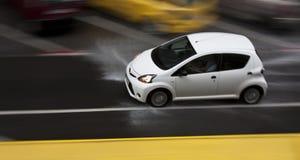 Дождливый день в городе: Управляя автомобиль в улице брызгая wat Стоковые Изображения RF