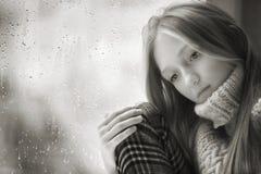 Дождливый день: унылая девушка на окне черно-белом Стоковые Фото