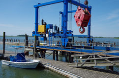 Доковый кран и шлюпка с морским взглядом Стоковая Фотография