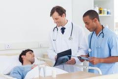 Доктора анализируя рентгеновский снимок Стоковые Изображения