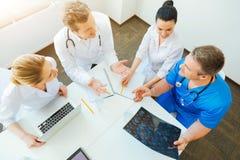 4 доктора беседуя над лучем x просматривают изображение пациента Стоковое фото RF