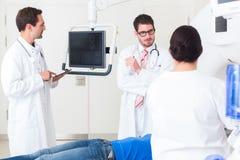Доктора в больнице на CT просматривают с пациентом Стоковое Изображение