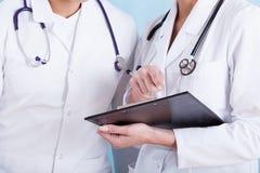 Доктора в медицинской белой рисберме с стетоскопами и доской сзажимом для бумаги Стоковое Изображение RF