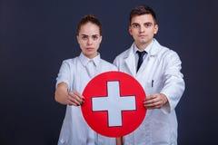 2 доктора в форме, держат один медицинский знак, белый крест в красном круге Стоковые Фотографии RF
