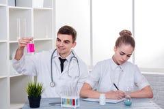 Доктора в форме, парень и девушка, парень рассматривают розовую жидкость в стеклянной склянке, девушка пишут что-то Стоковое Изображение