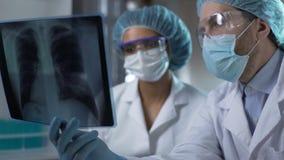 Доктора изучая рентгеновский снимок легких в лаборатории, анализируя и обсуждая диагноз сток-видео