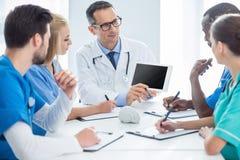 Доктора имея переговор и смотря таблетку Стоковое Фото