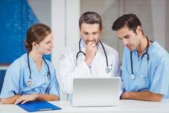 Доктора используя компьтер-книжку пока стоящ на столе Стоковое Изображение RF