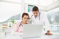 Доктора используя компьтер-книжку совместно на медицинском офисе Стоковые Изображения RF