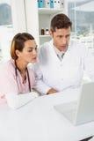 Доктора используя компьтер-книжку совместно на медицинском офисе Стоковые Фото