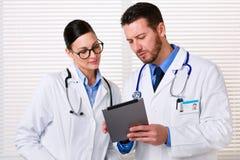 Доктора используя таблетку на работе Стоковое Изображение