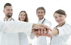 Доктора и медсестры в медицинской бригаде штабелируя руки Стоковое Изображение