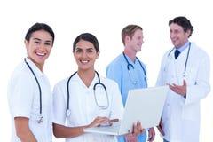 Доктора и медсестры обсуждая и используя компьтер-книжку Стоковые Изображения