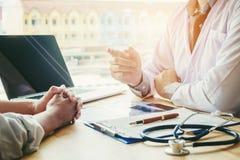 Доктора и пациенты сидят и говорят На таблице около окна Стоковые Изображения
