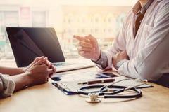 Доктора и пациенты сидят и говорят На таблице около окна Стоковое Фото