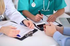 Доктора и пациент обсуждают что-то, как раз руки на таблице Стоковые Фото