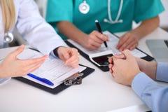 Доктора и пациент обсуждают что-то, как раз руки на таблице Стоковые Изображения RF
