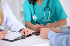 Доктора и пациент обсуждают что-то, как раз руки на таблице Стоковая Фотография