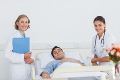 Доктора и пациент смотря камеру Стоковые Изображения RF