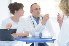 Доктора и сидеть медсестры ослабляя на офисе Стоковые Фотографии RF