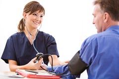 Доктора: Медсестра принимая кровяное давление Стоковое Изображение
