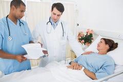 Доктора навещая женский пациент в больнице Стоковое Изображение RF