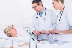 Доктора навещая женский пациент в больнице Стоковые Изображения