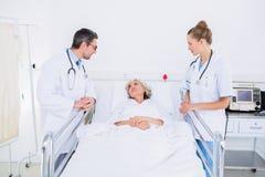 Доктора навещая женский пациент в больнице Стоковые Фотографии RF