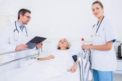 Доктора навещая женский пациент в больнице Стоковое фото RF