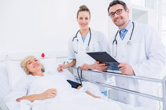 Доктора навещая женский пациент в больнице Стоковые Изображения RF