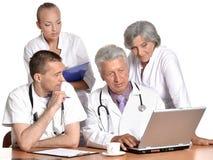 Доктора на таблице на белой предпосылке Стоковая Фотография RF