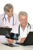 Доктора на таблице на белой предпосылке Стоковые Фотографии RF
