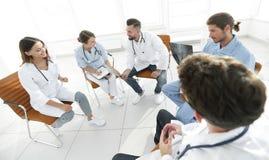 Доктора обсуждают рентгеновский снимок, сидя в офисе Стоковая Фотография