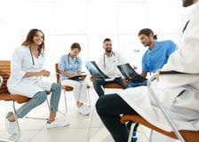 Доктора обсуждают рентгеновский снимок, сидя в офисе Стоковое Фото