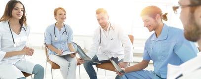 Доктора обсуждают рентгеновский снимок, сидя в офисе Стоковое фото RF