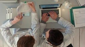 2 доктора обсуждая и работая совместно в медицинском офисе Взгляд сверху Стоковое фото RF