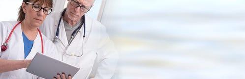 2 доктора обсуждая о медицинском заключении на таблетке Стоковые Фото