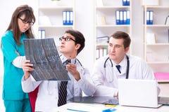 3 доктора обсуждая результаты развертки изображения рентгеновского снимка Стоковая Фотография