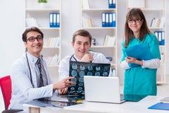3 доктора обсуждая результаты развертки изображения рентгеновского снимка Стоковые Изображения