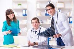 3 доктора обсуждая результаты развертки изображения рентгеновского снимка Стоковое фото RF